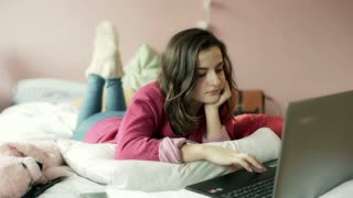 Teenage girl browsing internet on laptop and smiling to the camera