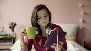 Teenage girl browsing internet on tablet and relaxing in her bedroom