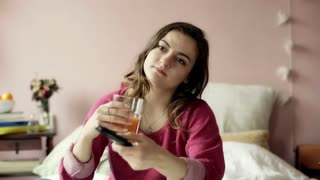Teenage girl drinking juice and changing channels on TV