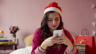 Teenage girl in Santas hat sitting on the bed and texting on smartphone