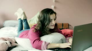 Teenage girl lying on her bed and typing on laptop