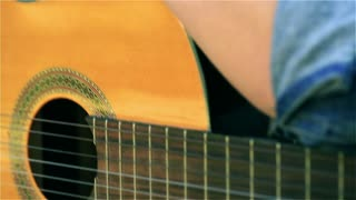 Teenage girl lying on the guitar and looking to the camera, steadycam shot