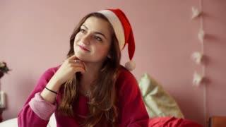 Teenage girl wearing Santas hat and smiling to the camera