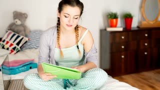 Teenager in pyjamas sitting on the bed and learning notes by heart, steadycam sh