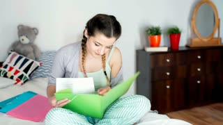 Teenager in pyjamas sitting on the bed and looking on the notes