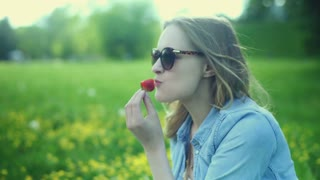 Thoughtful girl eating strawberry while sitting on the meadow