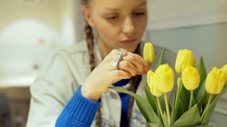 Thoughtful girl sitting alone in the cafe and touching yellow tulips