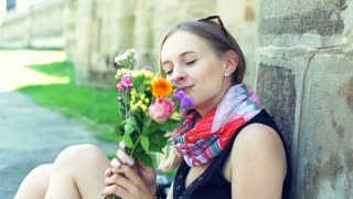 Thoughtful girl smelling bunch of colorful flowers and looking happy