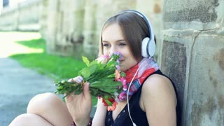 Thoughtful girl smelling bunch of flowers and listening music on headphones