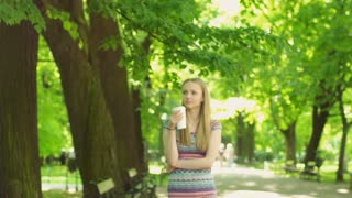 Thoughtful girl walking on path in the park and drinking coffee