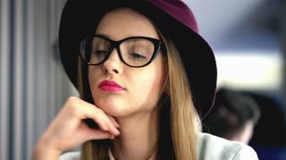 Thoughtful girl wearing glasses and burgundy hat in the cafe
