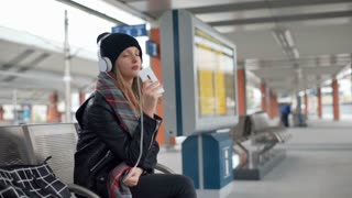 Thoughtful girl wearing warm clothes and listening music on a station