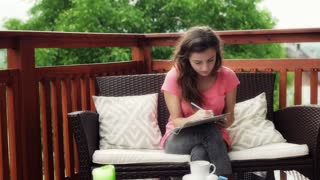 Thoughtful girl writing something in notebook and sitting on patio