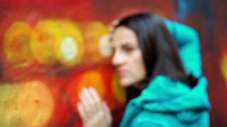 Thoughtful woman leaning on colorful wall, steadycam show, slow motion shot at 240fps