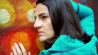 Thoughtful woman leaning on colorful wall, steadycam show, slow motion shot