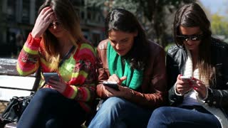 Three women sitting in the bench park and using smartphones