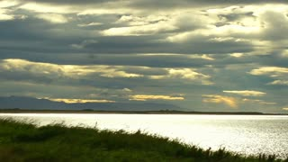Timelapse: beach, grass and calm sea. A cloudy sky. The sun sets