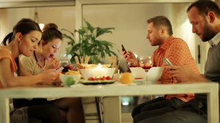Two couple eating dinner drinking wine and busy on smartphones.
