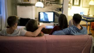 Two couples sitting on the sofa and watching tv