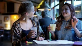 Two girl laughing in the cafe and drinking milkshakes