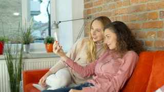 Two girl sitting on the sofa and having a videocall on smartphone