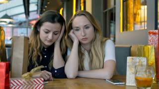 Two, sad girls sitting in the cafe and talking with each other, steadycam shot