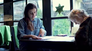 Two women sitting in the cafe and choosing meal from the menu, steadycam shot