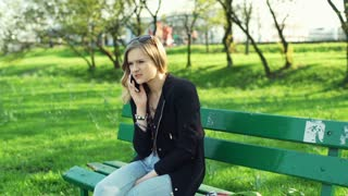 Unhappy girl talking on cellphone and sitting on the bench in park