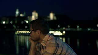 Unhappy man having problem and standing next to the river at night, steadycam sh
