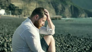 Unhappy man sitting on the shingle beach and looking thoughtful