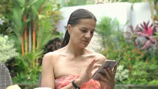 Attractive tanned woman looks absorbed while texting messages on smartphone, ste