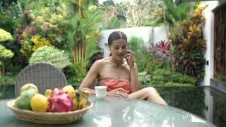 Attractive tanned woman relaxing in exotic place and chatting on cellphone, stea