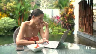 Attractive tanned woman sitting next to the pond with notebook and smiling to th