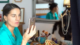 Attractive woman checking news on smartphone and looks shocked