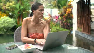 Attractive woman drinking juice and using laptop while sitting in exotic place,