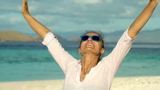 Attractive woman holding her hands up and looks happy on the beach, steadycam sh