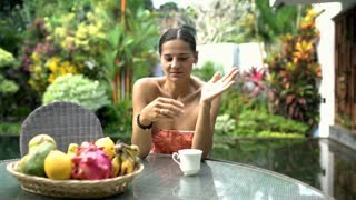 Attractive woman looks happy while drinking coffee and relaxing in exotic place,