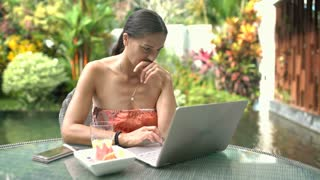 Attractive woman looks happy while using notebook outdoors, steadycam shot