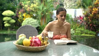 Attractive woman reading book and drinking coffee in exotic place, steadycam sho