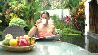 Attractive woman reading gazette in exotic place and drinking coffee, steadycam