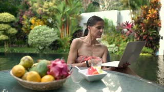 Attractive woman sitting in exotic place and using notebook, steadycam shot