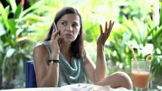 Attractive woman sitting in exotic restaurant and looks worried while speaking o