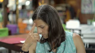 Attractive woman sitting in the restaurant and looks worried, steadycam shot