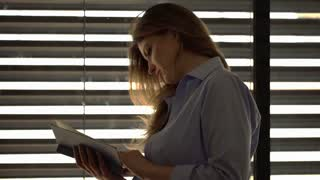Attractive woman standing next to the window and reading book