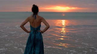 Attractive woman standing on the seaside during sunset and feels free, steadycam