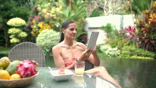 Attractive woman using tablet in exotic place and smiling to the camera, steadyc