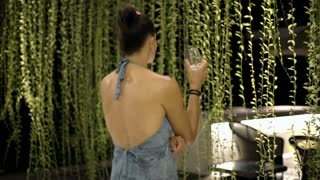 Attractive woman wearing dress with open back and drinking water in the garden a
