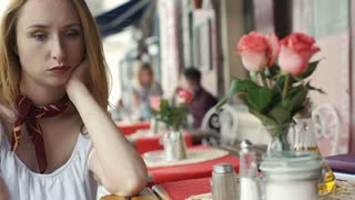 Beautiful, blonde girl sitting in the outdoor cafe and looks very sad, steadycam