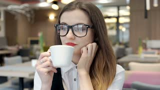 Beautiful businesswoman looks happy while relaxing in the cafe and drinking coff
