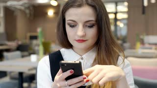Beautiful businesswoman sitting in the cafe and browsing internet on smartphone